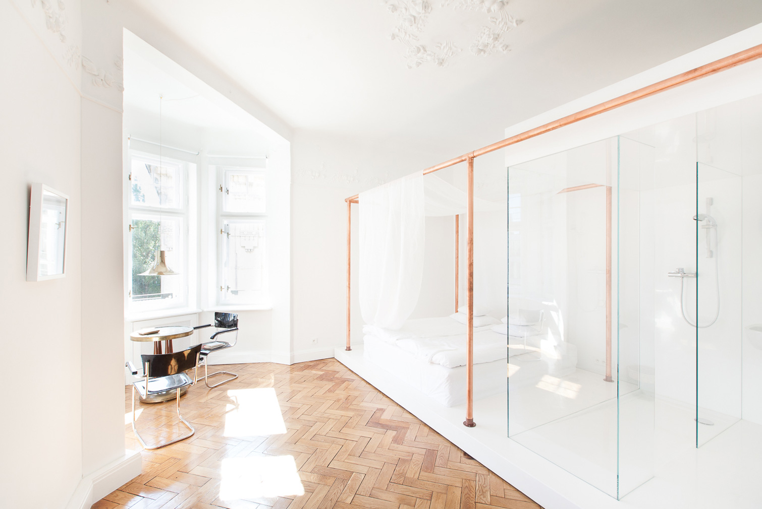 White bedroom suite with copper detailing and glass bathroom