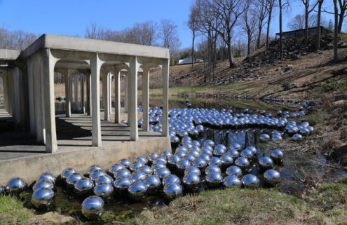 Yayoi Kusama floats 1,300 steel spheres in a pond at Philip Johnson's Glass House