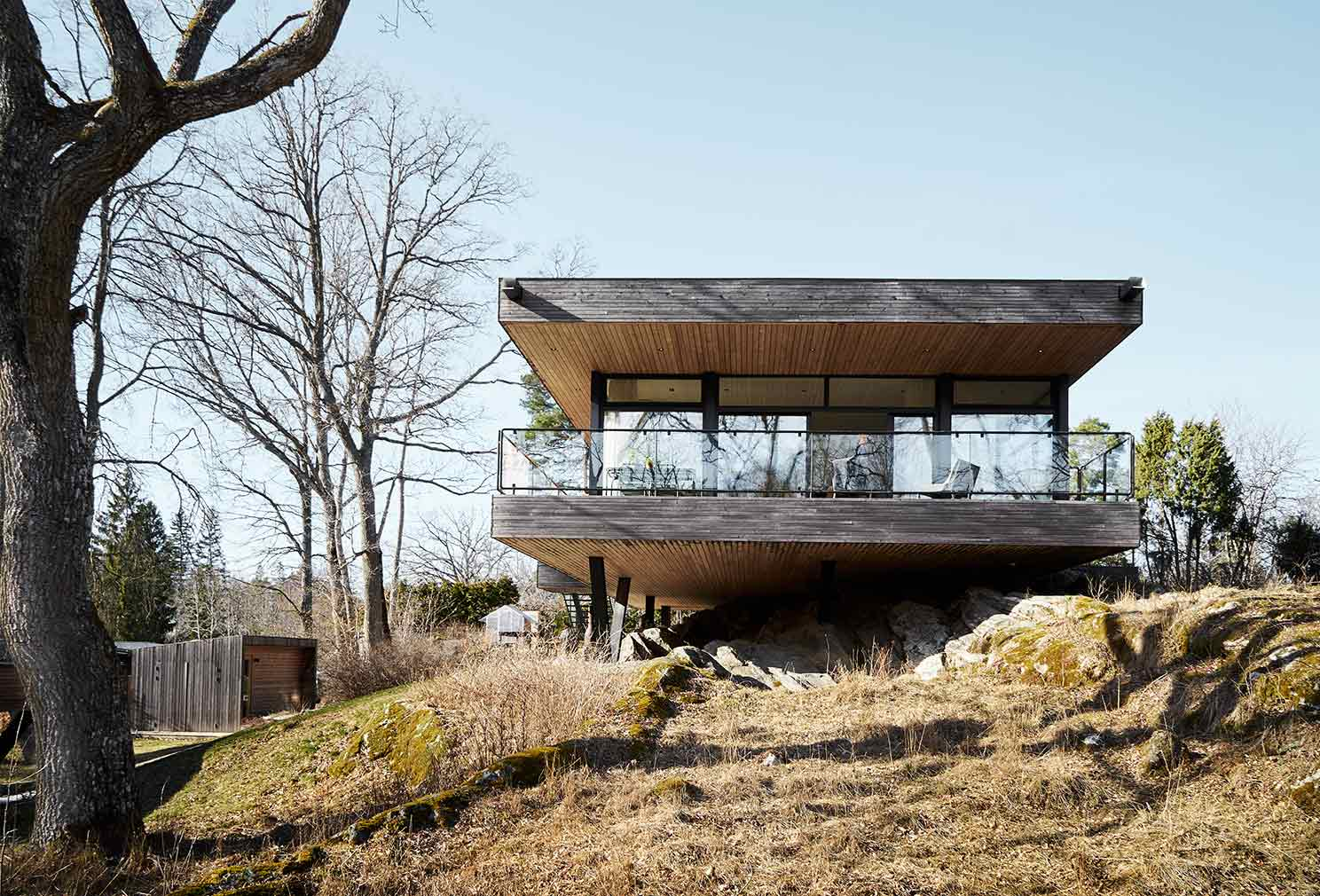 A minimalist Swedish home floats above a rocky outcrop in Värmdö