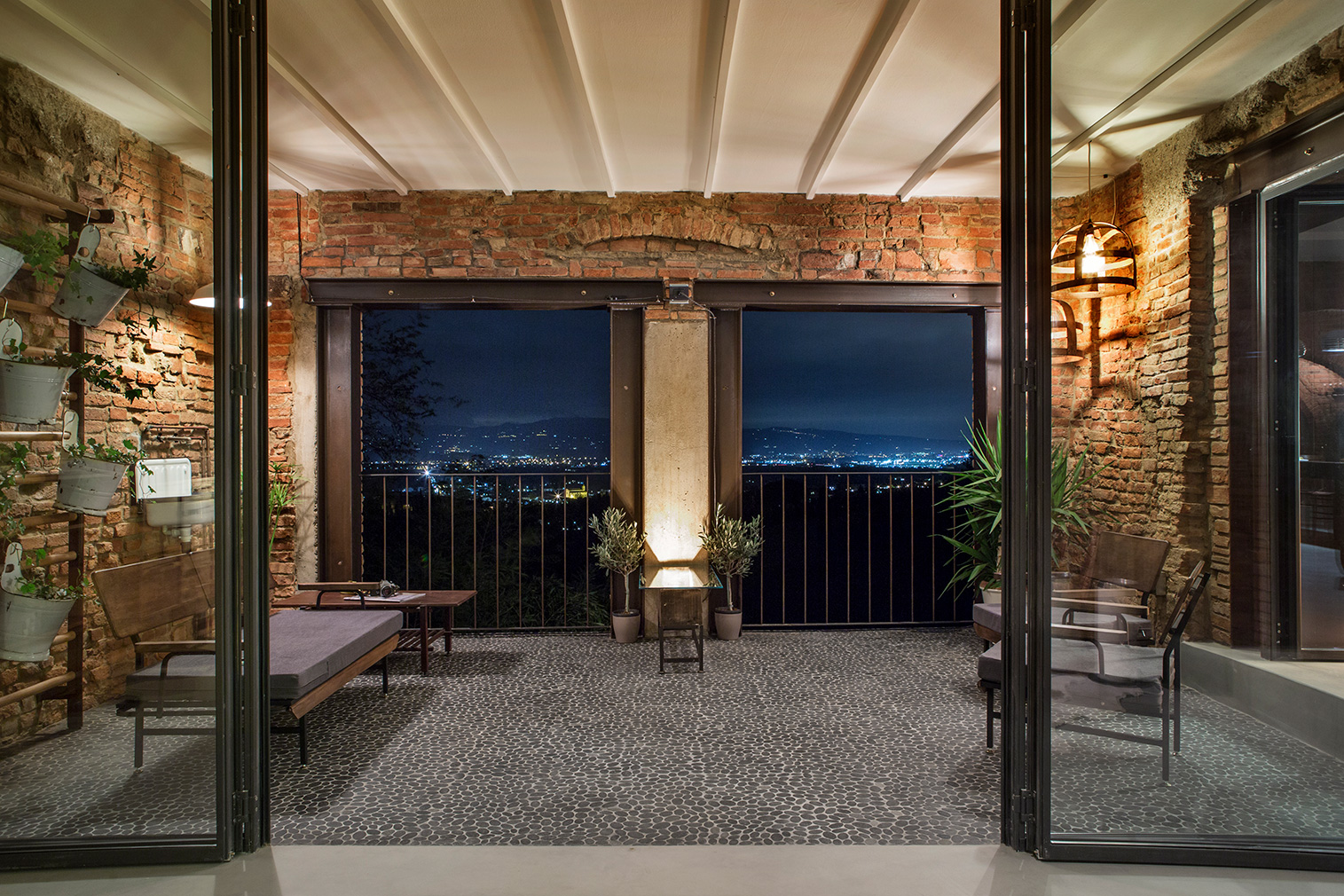 New full-height glass doors lead to a shaded balcony area with pebbled floors
