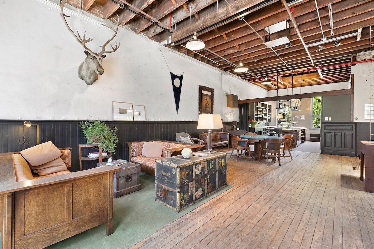 converted firehouse for sale in brooklyn's williamsburg: rustic meets industrial in the living room via exposed ceiling joists and wooden flooring