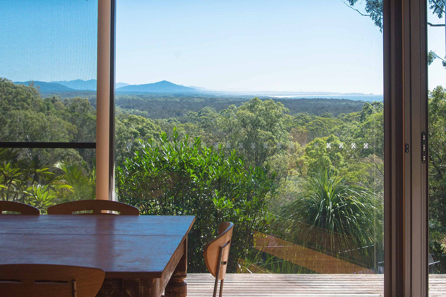 Floor-to-ceiling windows frame views of the bush from Way Way House