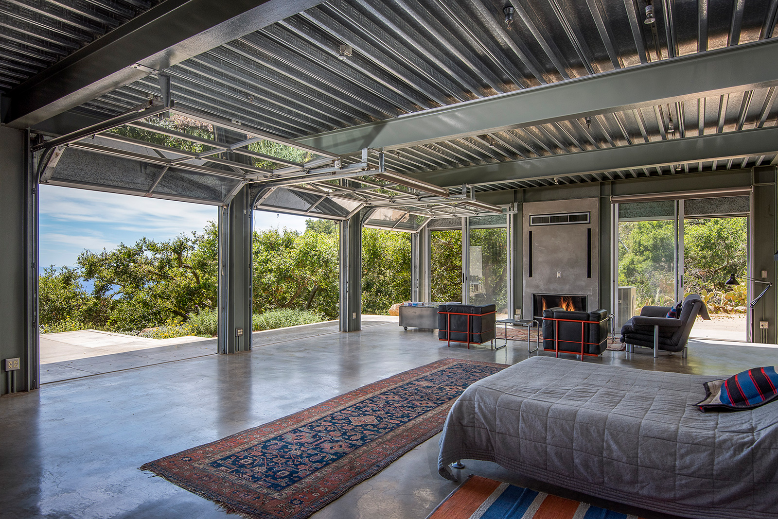 Concrete floors, steel beams, corrugated ceilings and rolling steel-framed doors feature inside the industrial style Barton Myers Residence, for sale in Santa Barbara via Sotheby's International