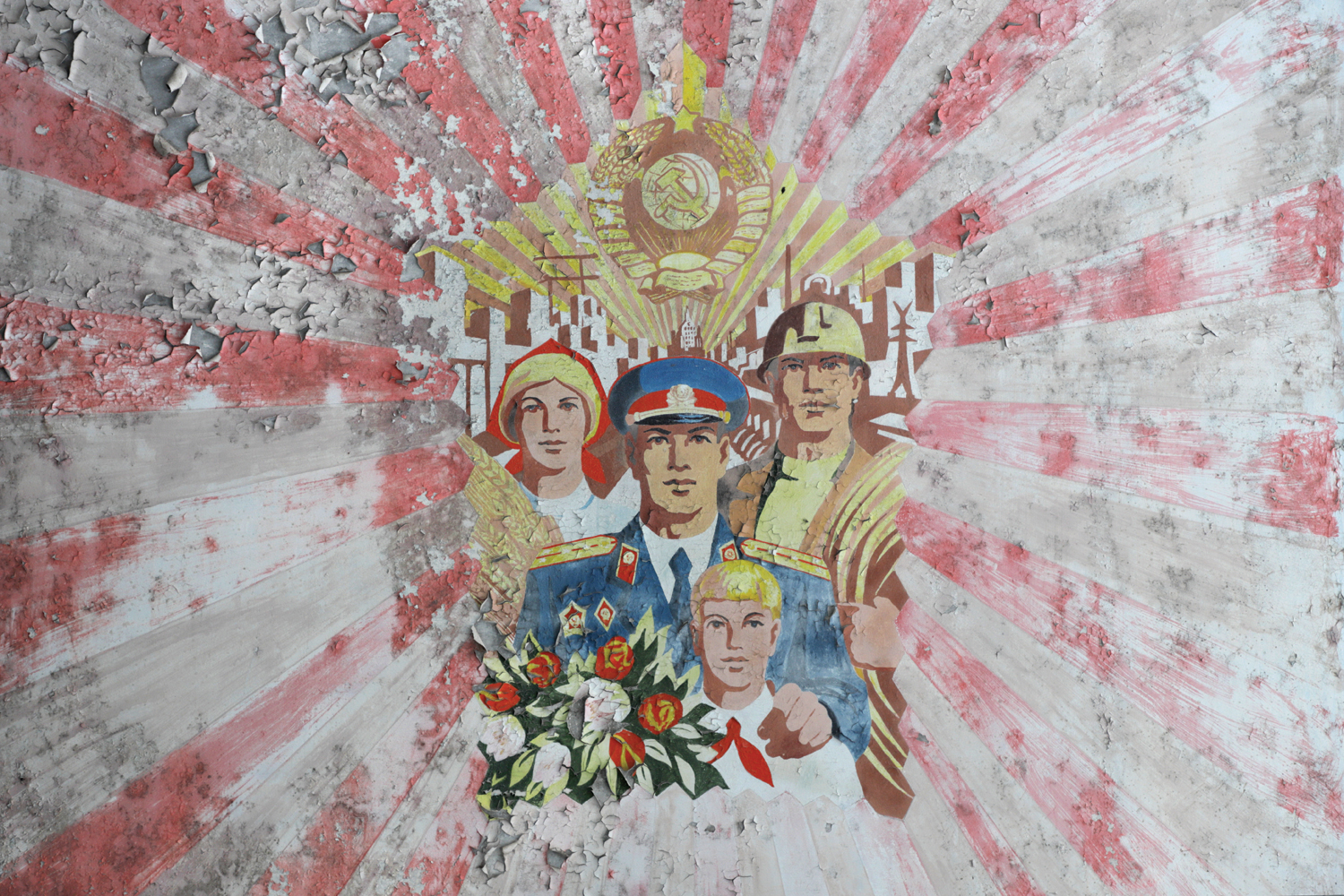 Mural on a residential building, Heroes of Stalingrad Street, Pripyat. This Socialist-realist mural depicts virtuous citizens (a farmer, a firefighter, a police officer, and a Young Pioneer) under a radiant Soviet crest. © Darmon Richter / FUEL Publishing