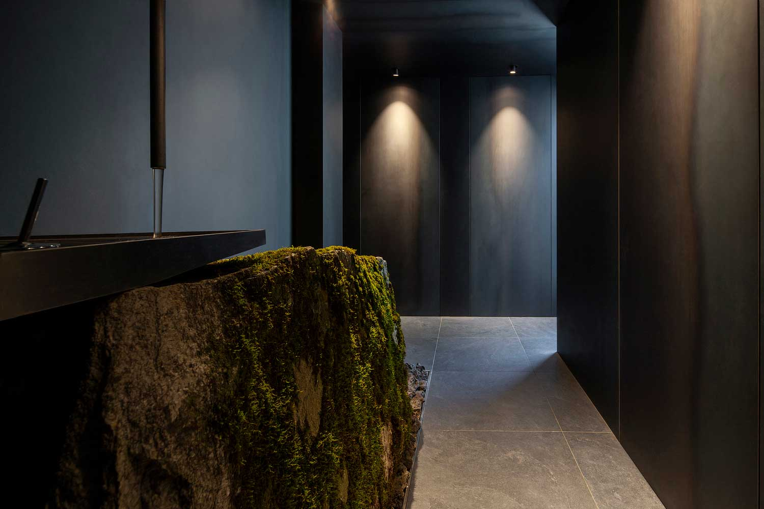 The bathroom features a sink that rests atop a moss-covered boulder