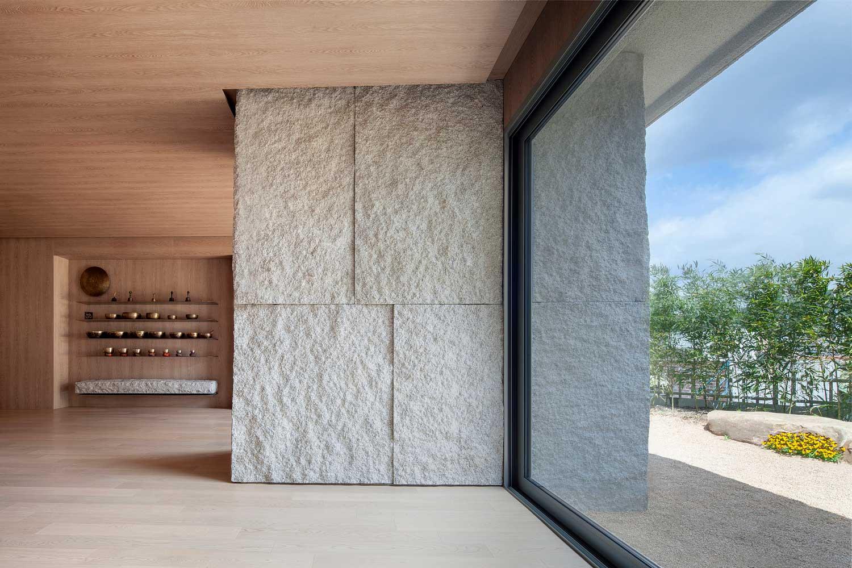 Oversized window panes overlook zen gardens in the Yoga Studio's grounds